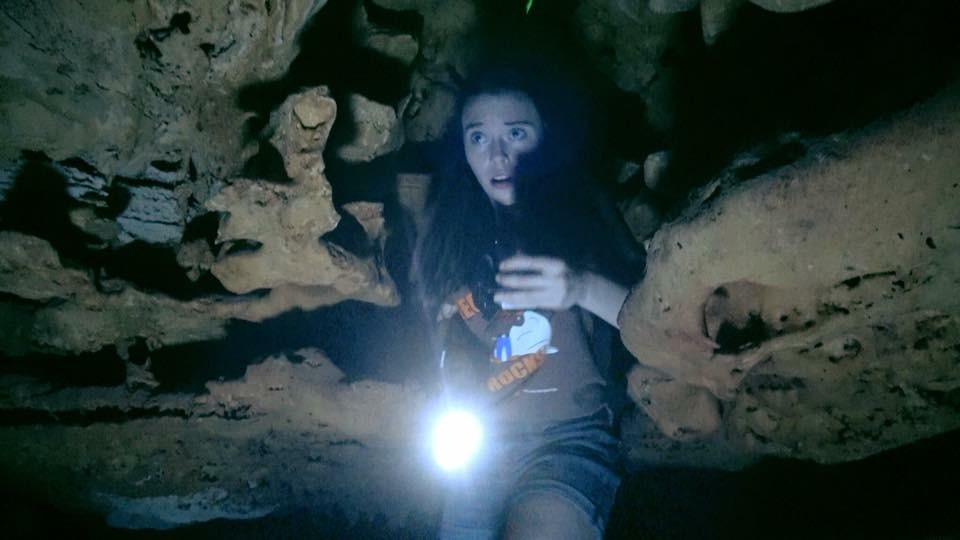 Woman with flashlight in cave